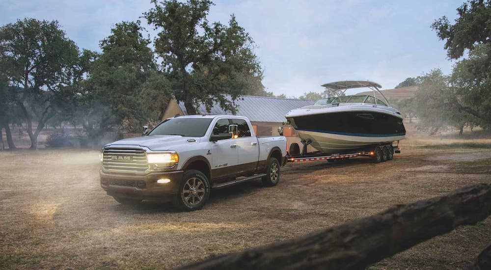 A white 2020 Ram 2500 is towing a boat on a ranch after winning the 2020 Ram 2500 vs 2020 Chevy Silverado 2500HD comparison.