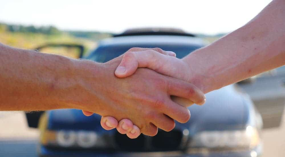 A close up is shown of two hands shaking in front of a parked car.