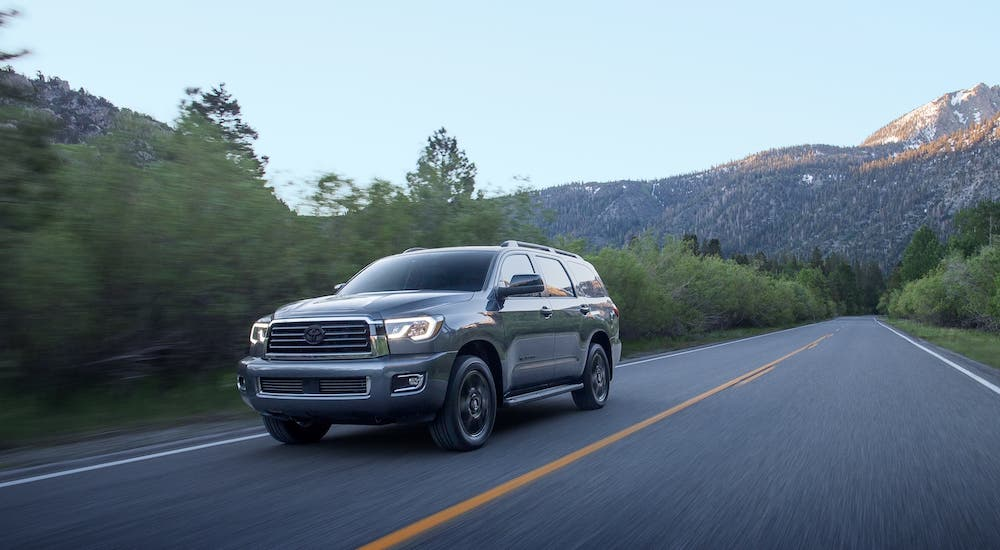 A gray 2020 Toyota Sequoia is driving on a rural highway.