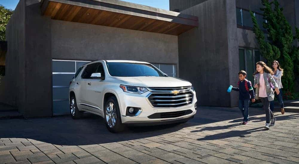 A family is walking towards a white 2020 Chevy Traverse that is parked in their driveway.