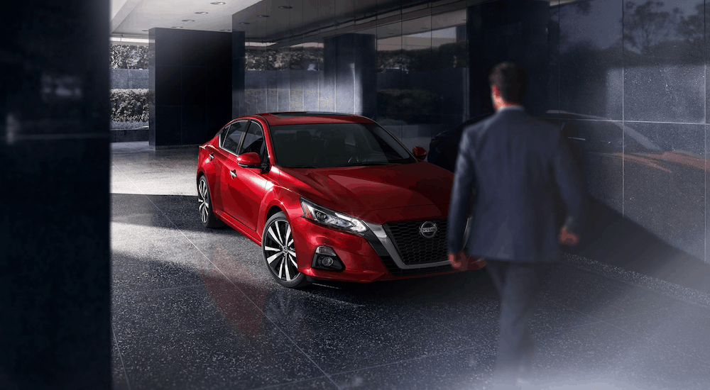 A man is walking towards a red 2020 Nissan Altima after losing the 2020 Ford Fusion vs 2020 Nissan Altima comparison.