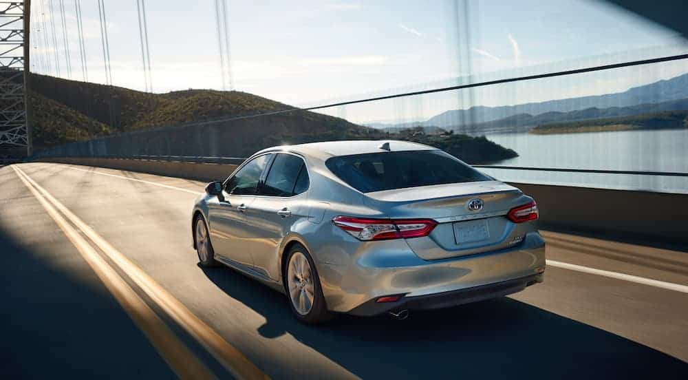A silver 2020 Toyota Camry is driving away on a bridge next to water.
