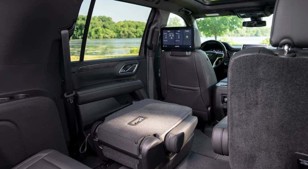 A folded middle seat is shown inside a 2021 Chevy Suburban from the cargo area.