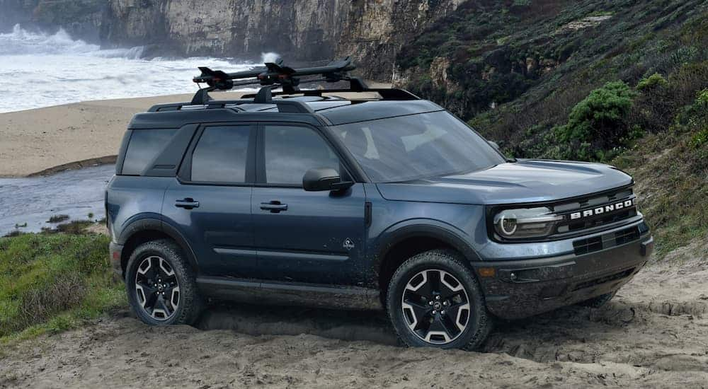 A dark blue 2021 Ford Bronco Sport is parked in the sand in front of the ocean and cliffs.