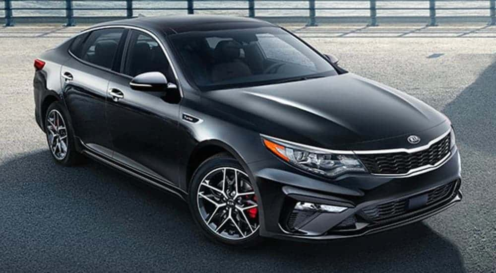 A black 2020 Kia Optima is parked in front of a pier.