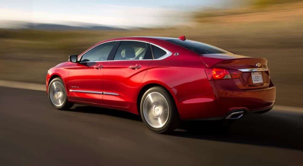 A red 2014 Chevy Impala is driving past blurred trees.