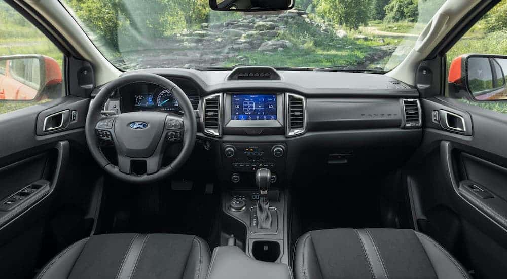 The black interior is shown from the back seat on a 2021 Ford Ranger Tremor Lariat.