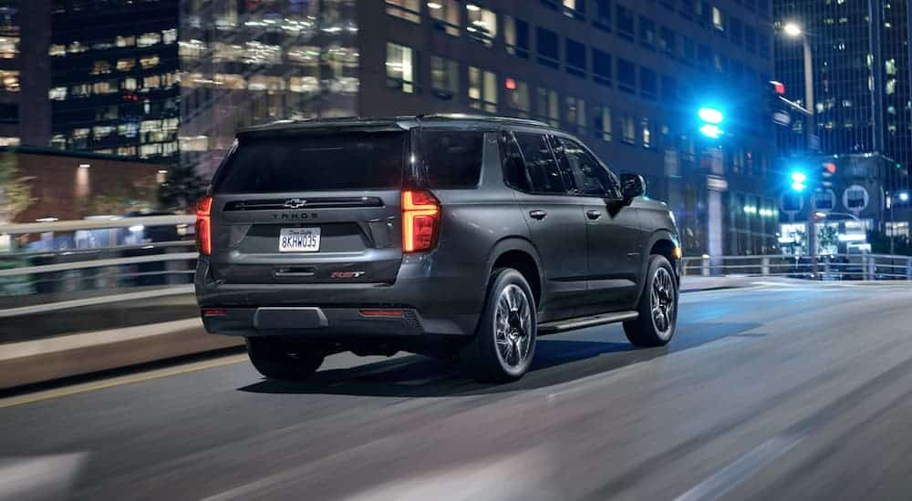 A silver 2021 Chevy Tahoe is driving through a city at night.