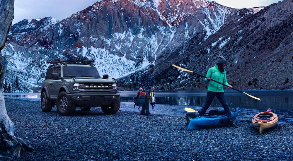A grey 2021 Ford Bronco is parked on a river bed where a couple is prepping to kayak.