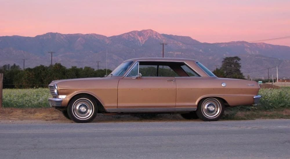 A tan 1863 Chevy Nova is parked in front of a pink sunset.
