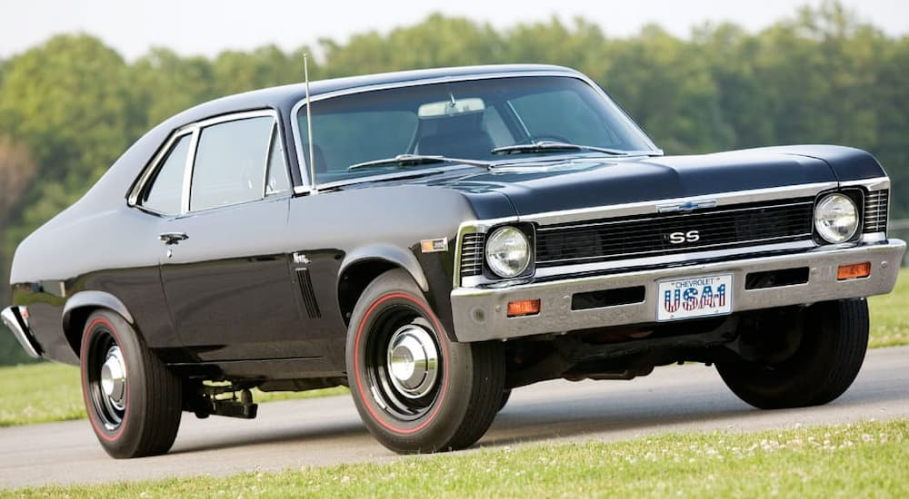 A black 1969 Chevy Nova is parked in the grass.