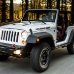 A white 2013 Jeep Wrangler Rubicon is driving.