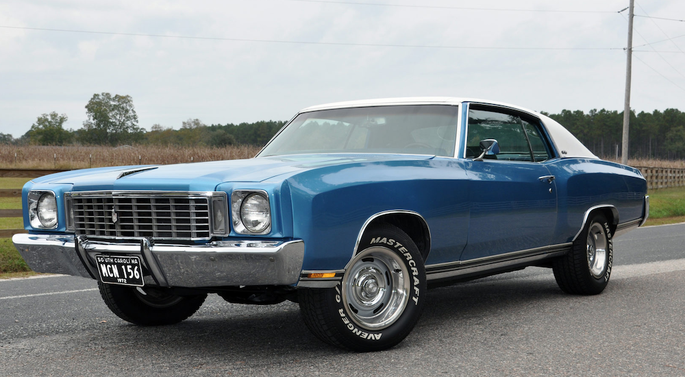 A blue mid 70s Chevy Monte Carlo is parked after leaving one of the local Chevy Dealerships.