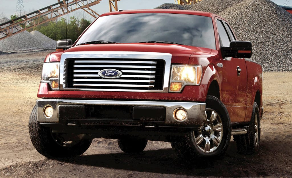 A 2011 Red Ford F-150 from the front in a gravel pit