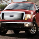 A 2011 Red Ford F-150 is parked with lights on.