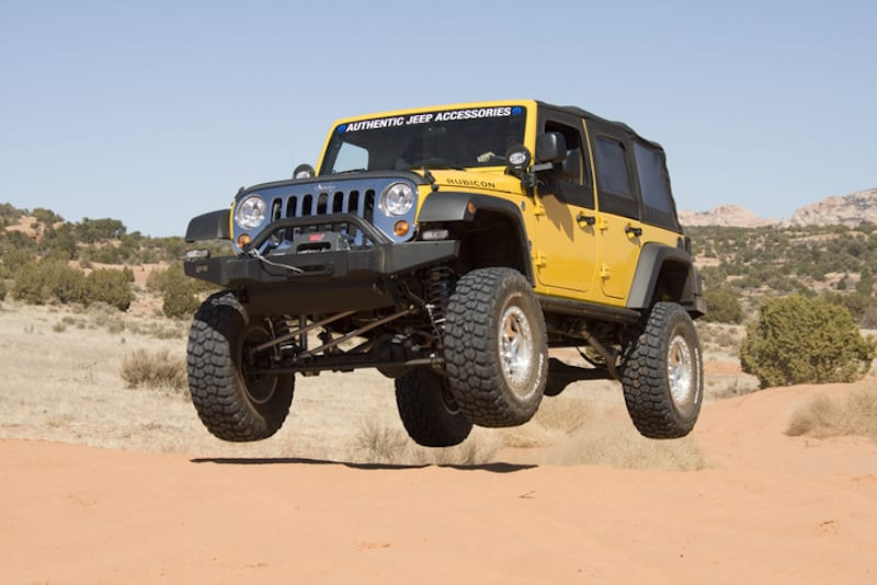 A yellow modified used Jeep Wrangler is jumping in the desert.