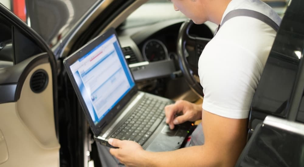 A mechanic is checking the OBD2 readings on his laptoip in a car to give a car repair estimate.