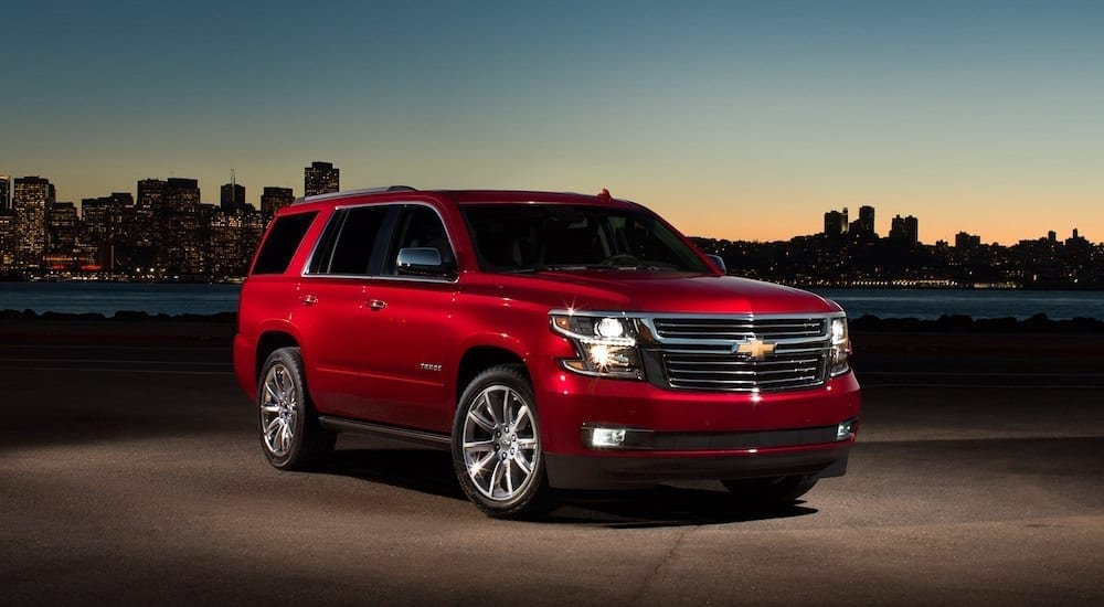 Red 2018 Chevrolet Tahoe in front of cityscape at dusk