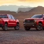 2 Red 2018 Chevy Silverados in front of a canyon at sunset