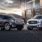 Silver 2019 GMC Yukon and Black Yukon Denali in front of glass building