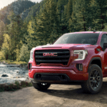 Red 2019 GMC Sierra 1500 with woodland river in back