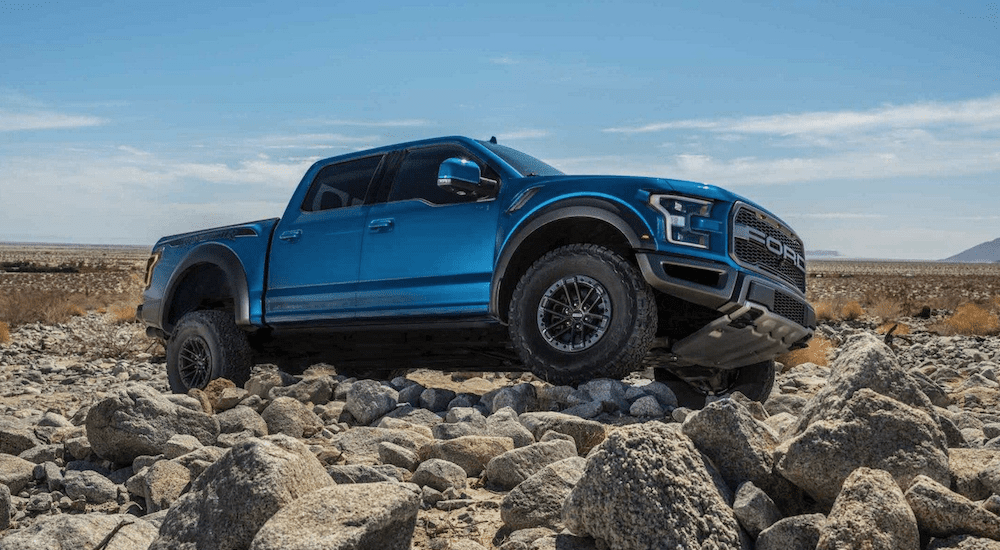 Blue 2019 Ford Raptor climbing rocks