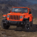 A bright orange 2019 Jeep Wrangler climbs a rocky mountain