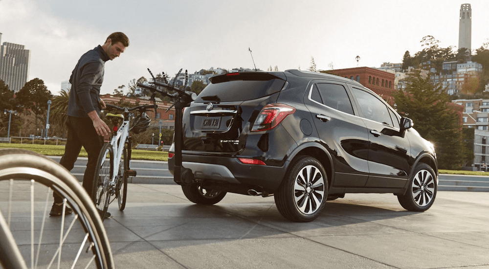 A man about to load a bike onto a black 2019 Buick Encore