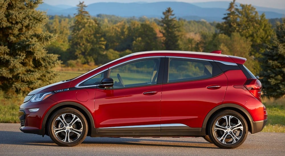 A red 2019 Chevrolet Bolt EV with trees and mountains in back