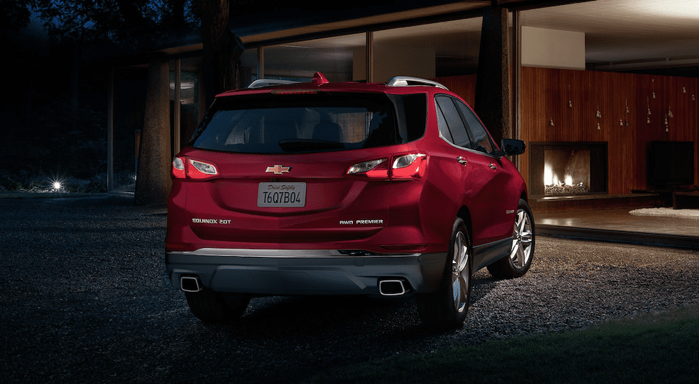The back of a red 2019 Chevy Equinox in front of a house at night