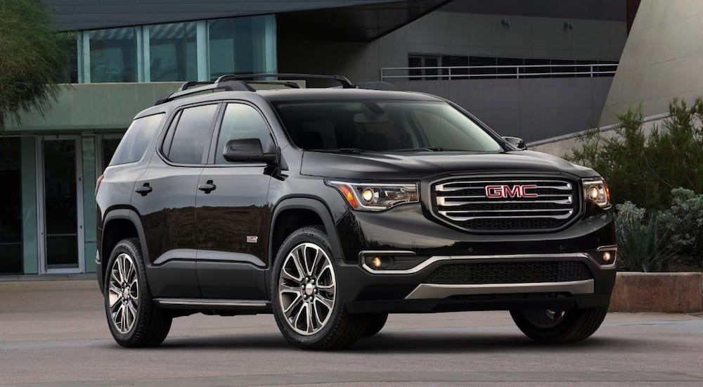 A black 2019 GMC Acadia All Terrain parked in front of a house