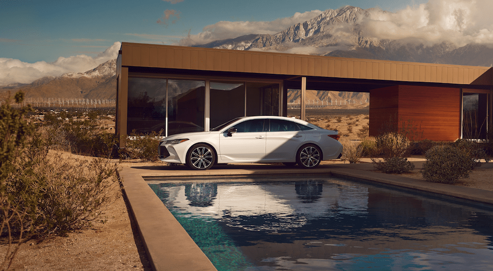 A white 2019 Toyota Avalon at a desert mansion with pool and wind turbines