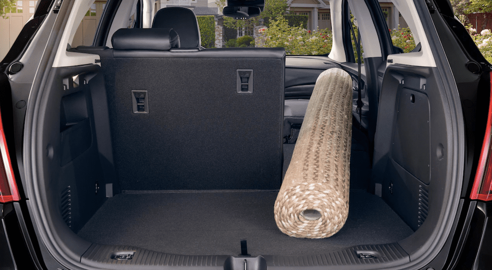 The cargo space of the 2019 Buick Encore is shown to hold a rug with the seats folded down in a comparison of the 2019 Buick Encore vs 2019 Honda HR-V.