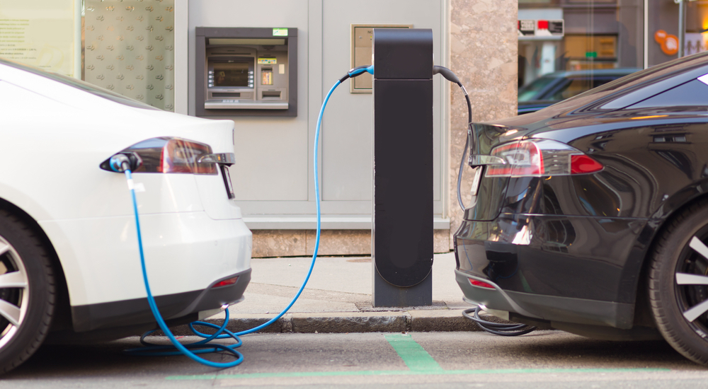 A black sedan and a white sedan are charging at an electric car station.