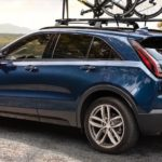A blue 2019 Cadillac XT4 is parked with bikes on the top and a view.