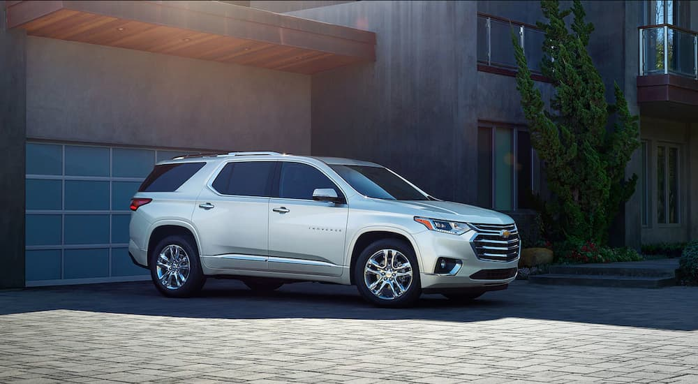 A white 2019 Chevy Traverse is parked outside a modern house.