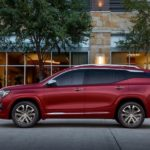 A red 2019 GMC Terrain Denali is parked in front of shops.