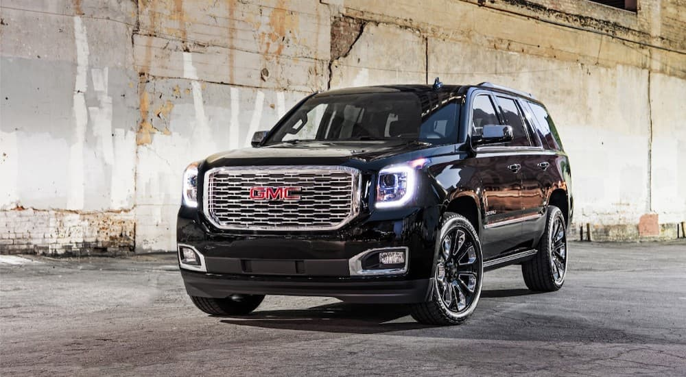 A black 2019 GMC Denali is parked in front of a crumbling wall. It is in the lineup of GMC SUVs.