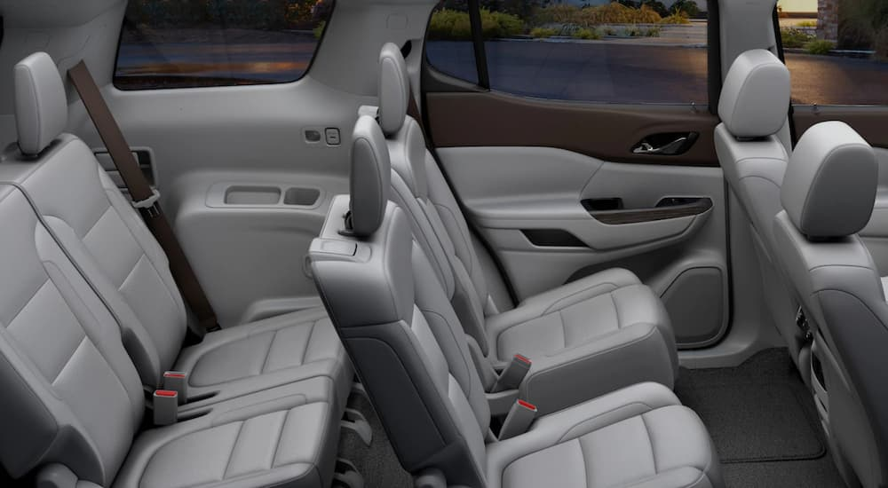 The grey interior of the 2019 GMC Acadia is showing the two back rows of seating. Check out interior when comparing the 2019 GMC Acadia vs 2019 Nissan Pathfinder.