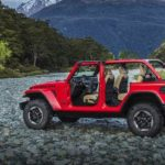 A red 2019 Jeep Wrangler, a great option for a Jeep lease deal, is parked on rocks in front of a mountain.