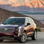 A maroon 2019 Cadillac XT5 with mountains and fields in the background.