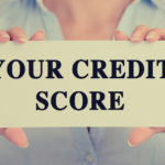 A sign saying your credit score is being held up by a business women.