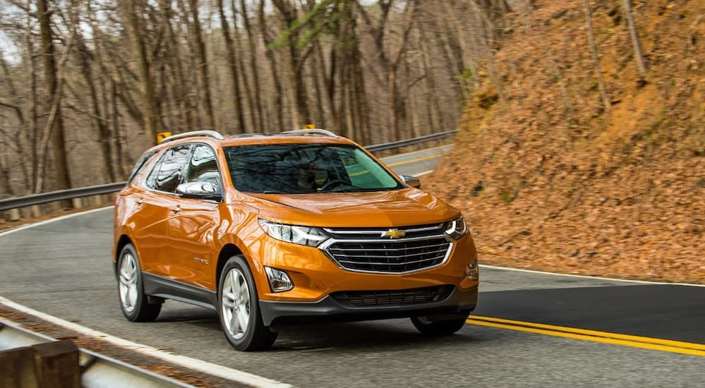 An orange 2019 Chevy Equinox is driving on a road with trees in the background.