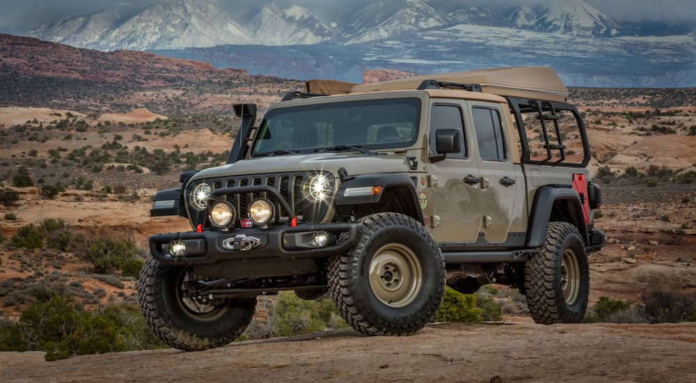 The tan 2019 Jeep Gladiator Wayout build is shown in a desert with mountains behind it.
