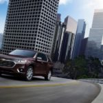 A burgundy 2019 Chevy Traverse is driving out of the city.