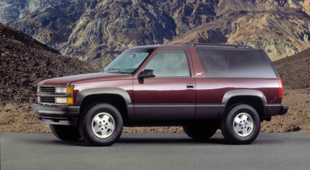 A maroon 1995 Chevy Tahoe Sport is parked in front of mountains.