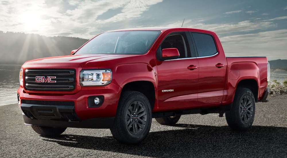 A red 2019 GMC Canyon, which wins when comparing the 2019 GMC Canyon vs 2019 Nissan Frontier, is on a lake shore.