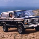 A family is in their black 1983 Ford Bronco in front of the ocean.