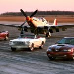 A white 1965 Ford Mustang is between two red 2004 Mustangs in front of a P-51.