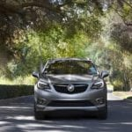 A silver 2020 Buick Envision is driving on a tree lined neighborhood road.